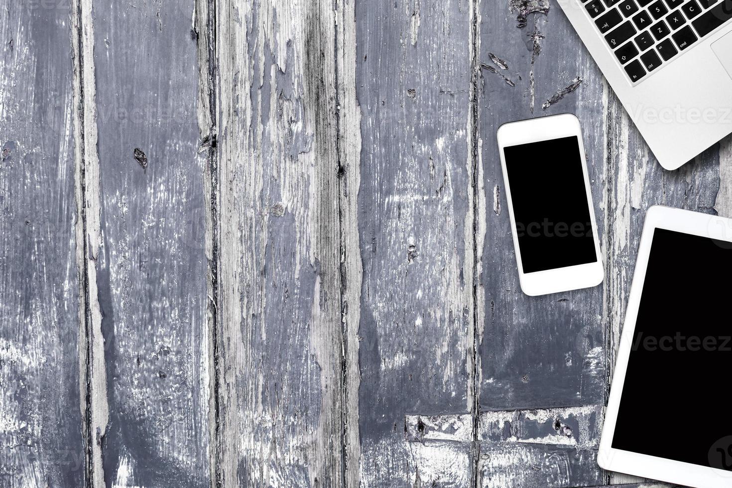 telefone tablet computador em uma mesa de madeira foto
