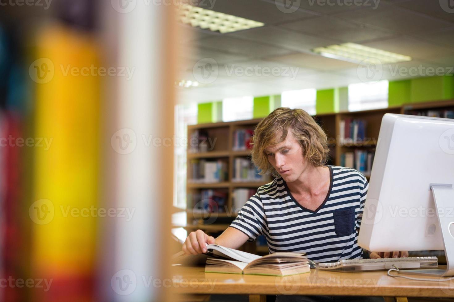 aluno estudando na biblioteca com o computador foto