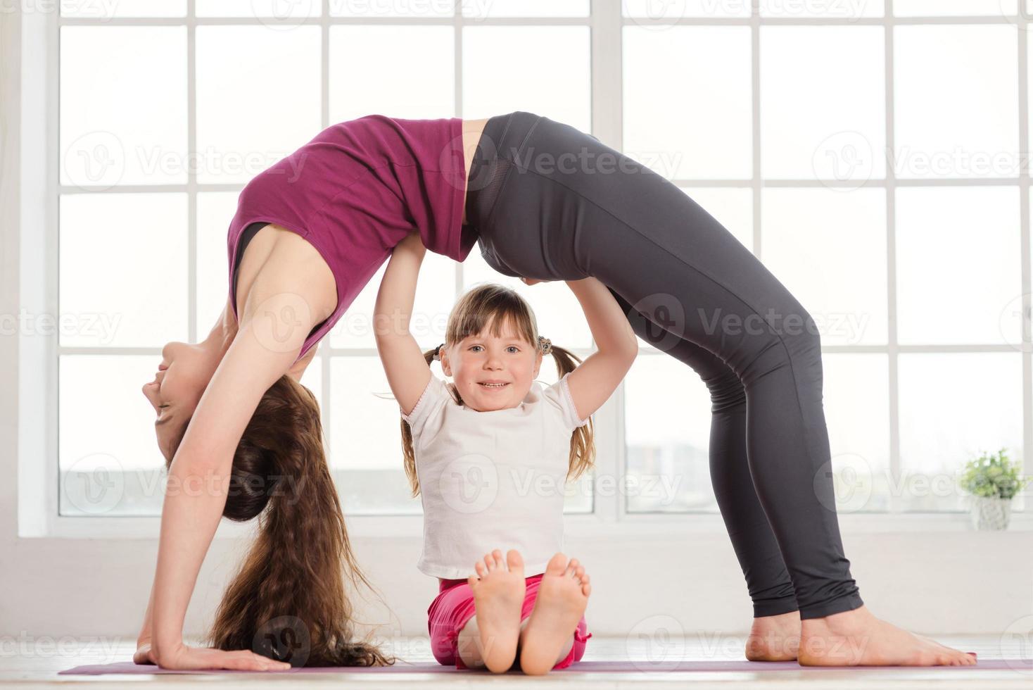 jovem mãe e filha fazendo exercícios de ioga foto