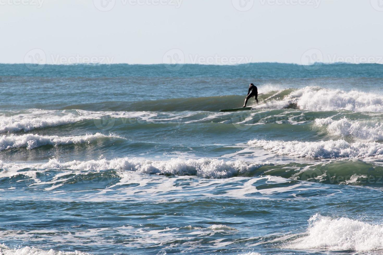 surfista preto roupa de mergulho surfando a onda foto