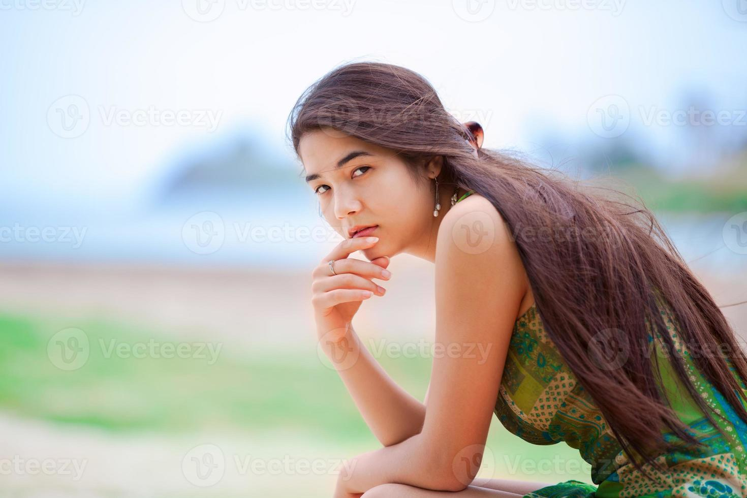 linda menina adolescente biracial sentado na praia tropical, pensando foto