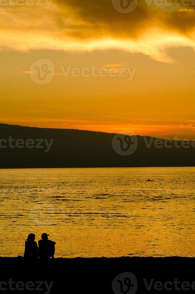 casal adulto em silhueta na praia foto