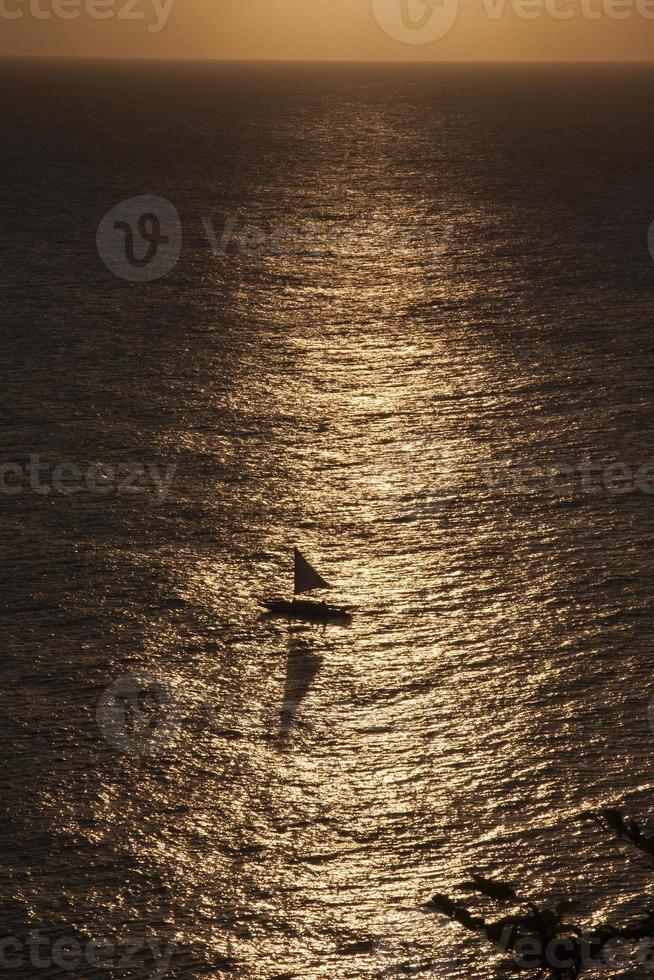 barco a vela ao pôr do sol foto