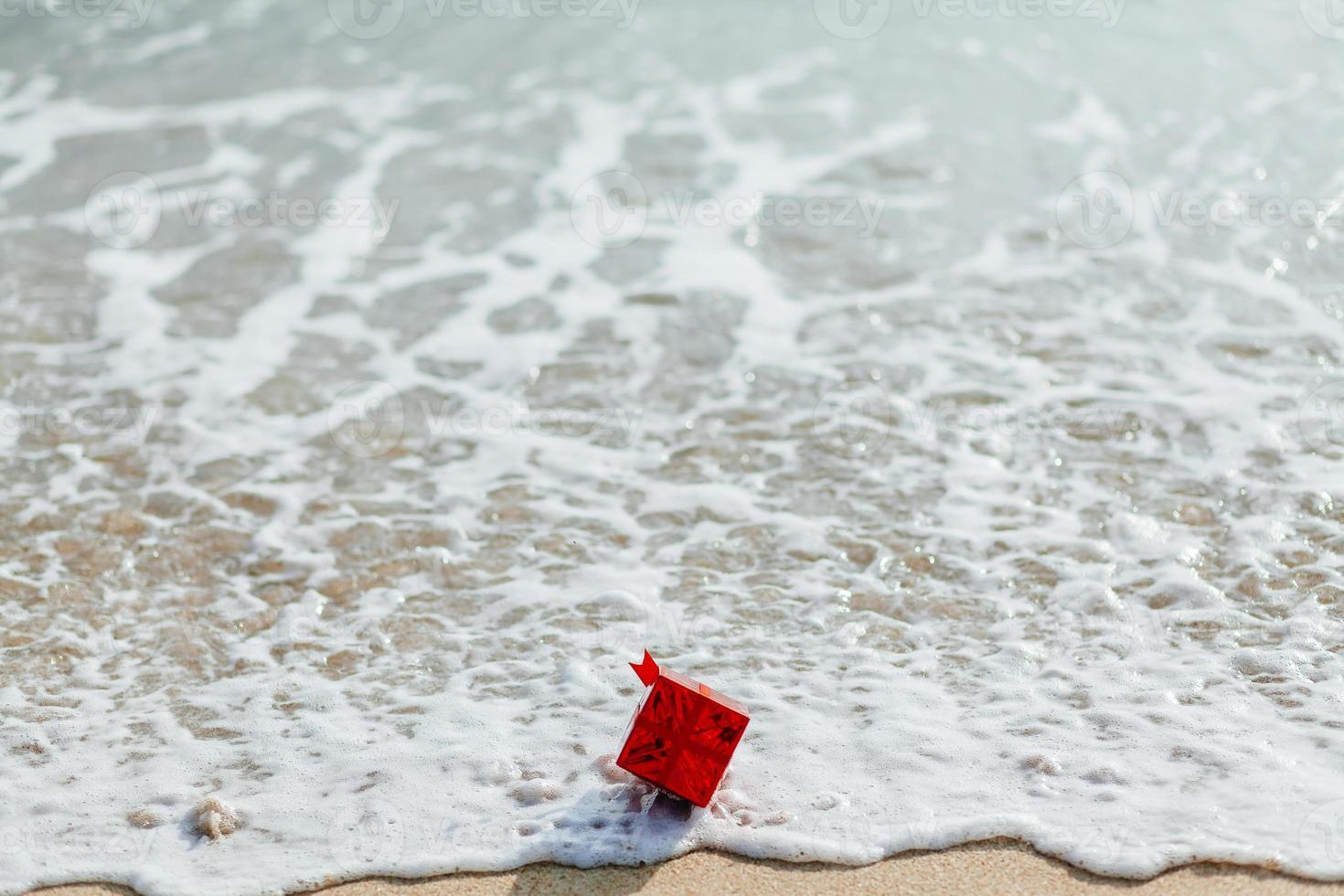 caixa de presente vermelha no mar foto