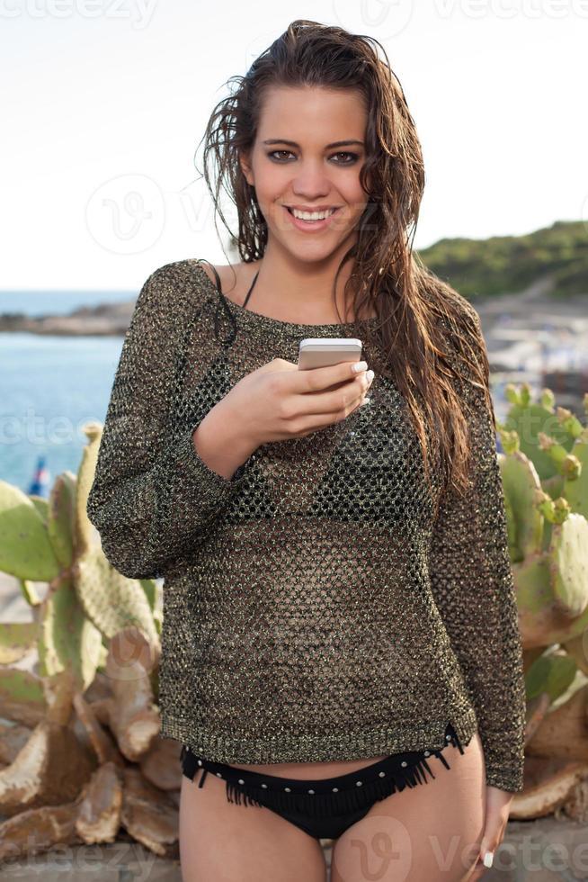 garota na praia mandava um smartphone foto