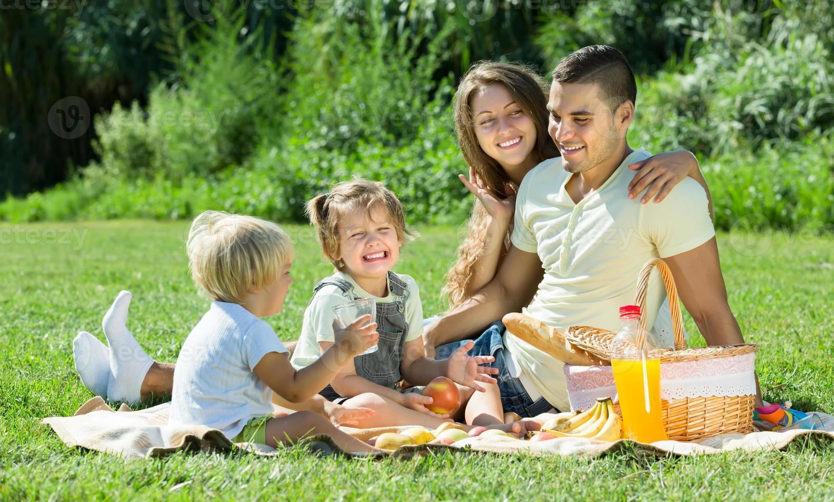 família de quatro pessoas fazendo piquenique foto