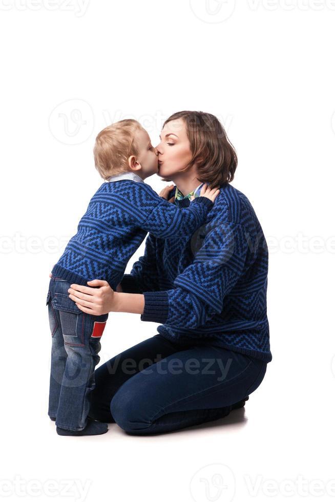 jovem mãe beijando amorosamente seu filho pequeno. isolado no branco foto