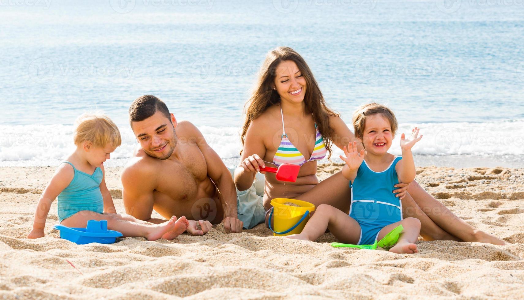 família de quatro na praia foto