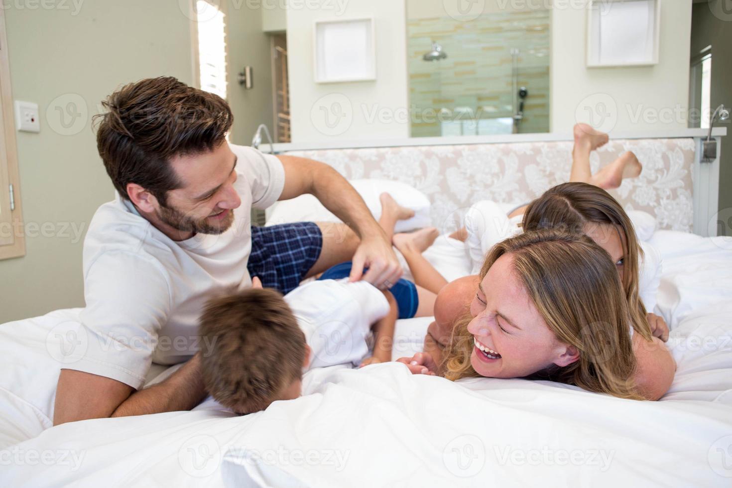 família feliz brincando na cama foto