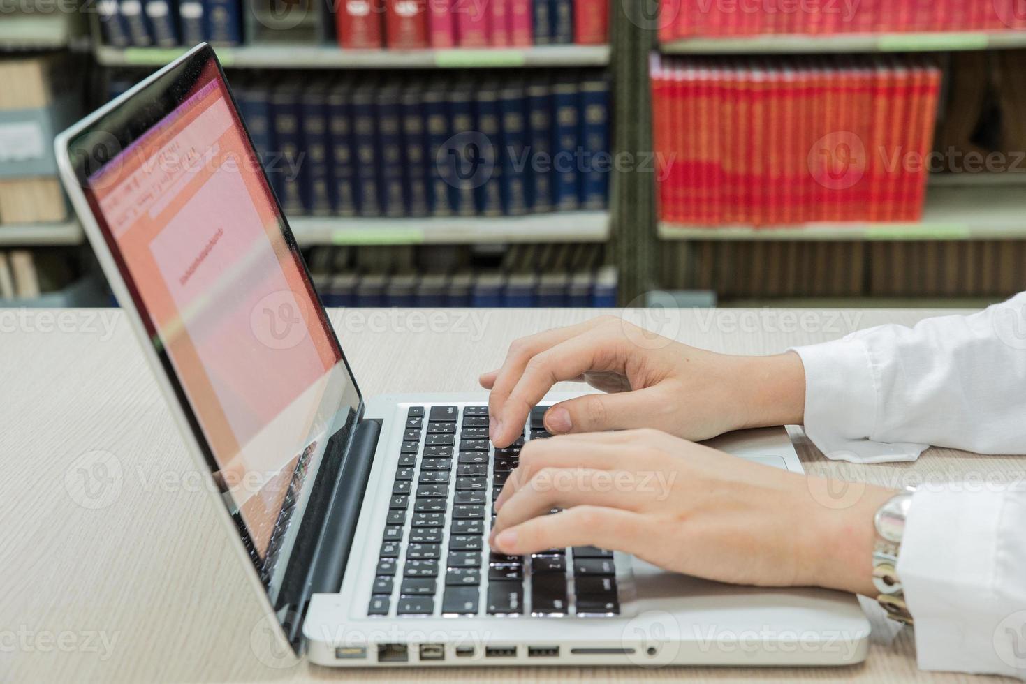 adolescente usando laptop na biblioteca foto