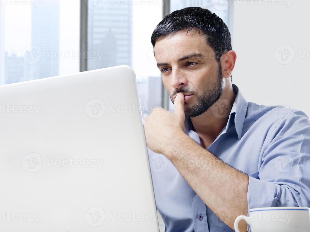 empresário atraente trabalhando no computador na mesa de escritório foto
