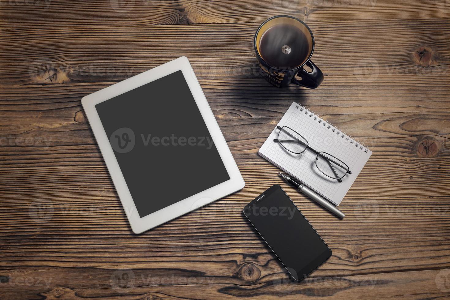 computador tablet, telefone inteligente, xícara de café, bloco de notas e óculos foto