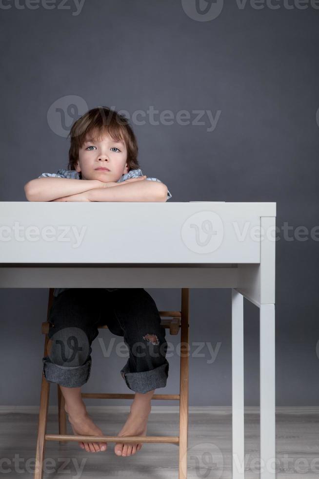estudante de pensamento sentado na mesa foto