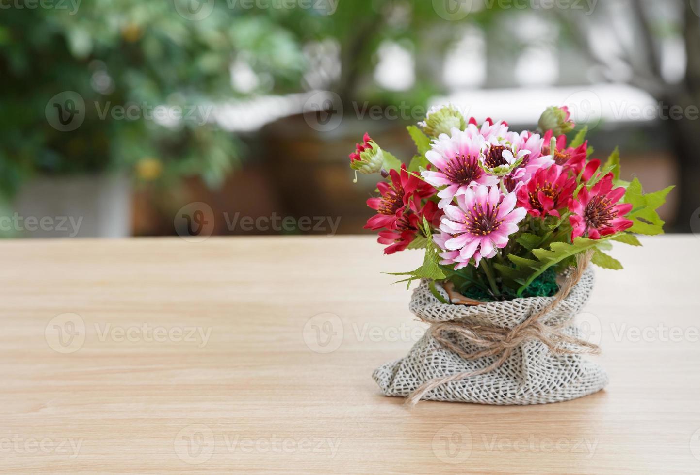 flor decorativa na mesa de madeira foto