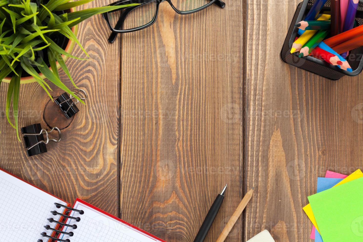 mesa de escritório com flor, bloco de notas em branco e suprimentos foto
