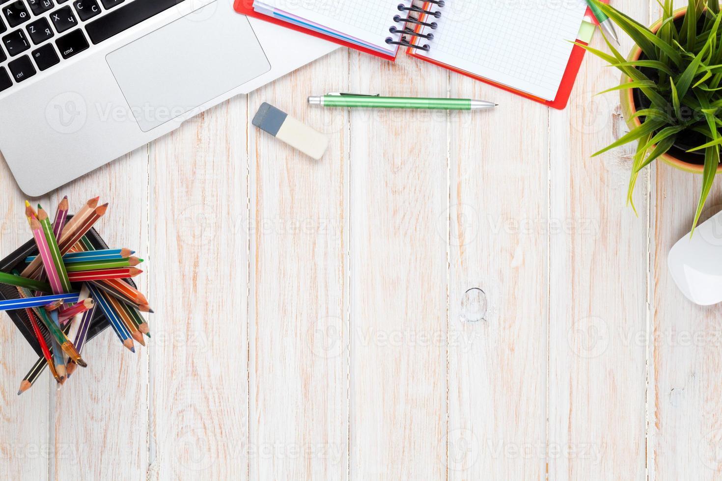 mesa de escritório de madeira com planta, laptop, borracha e lápis foto
