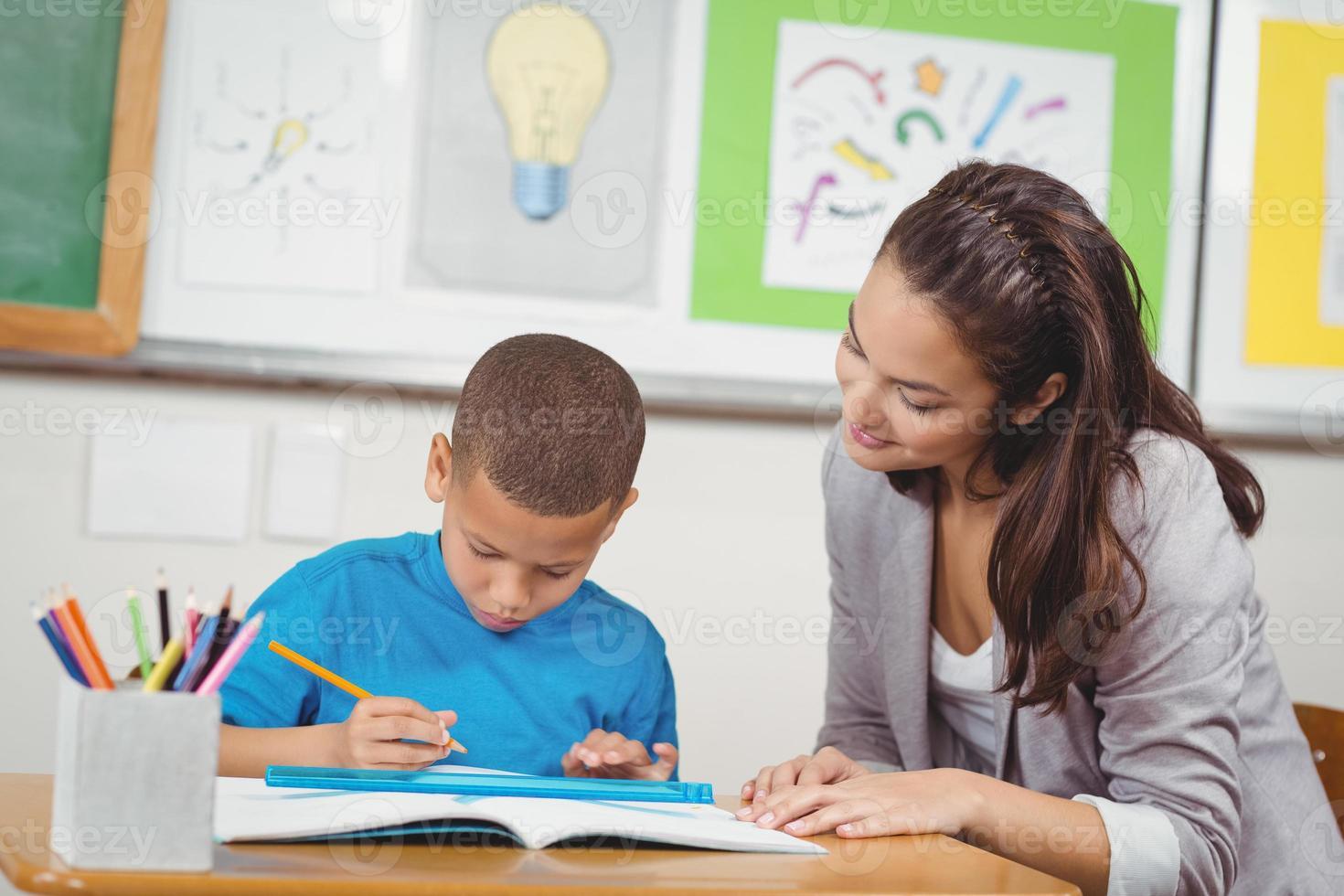 professor bonito, ajudando o aluno em sua mesa foto