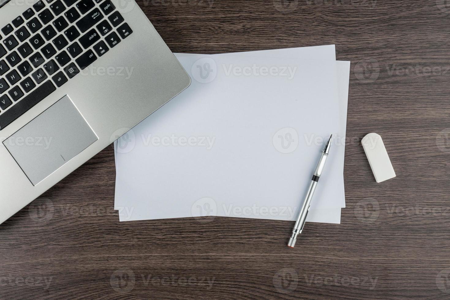 laptop, caneta de papel e borracha na mesa de trabalho foto
