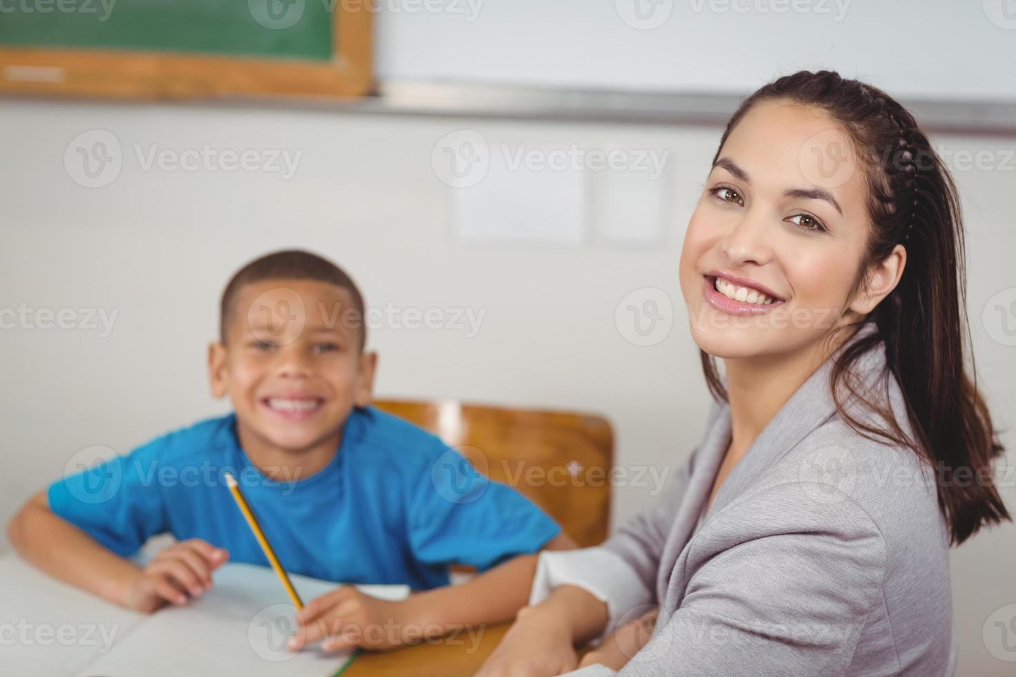 professor sorridente e seu aluno sentado na mesa foto