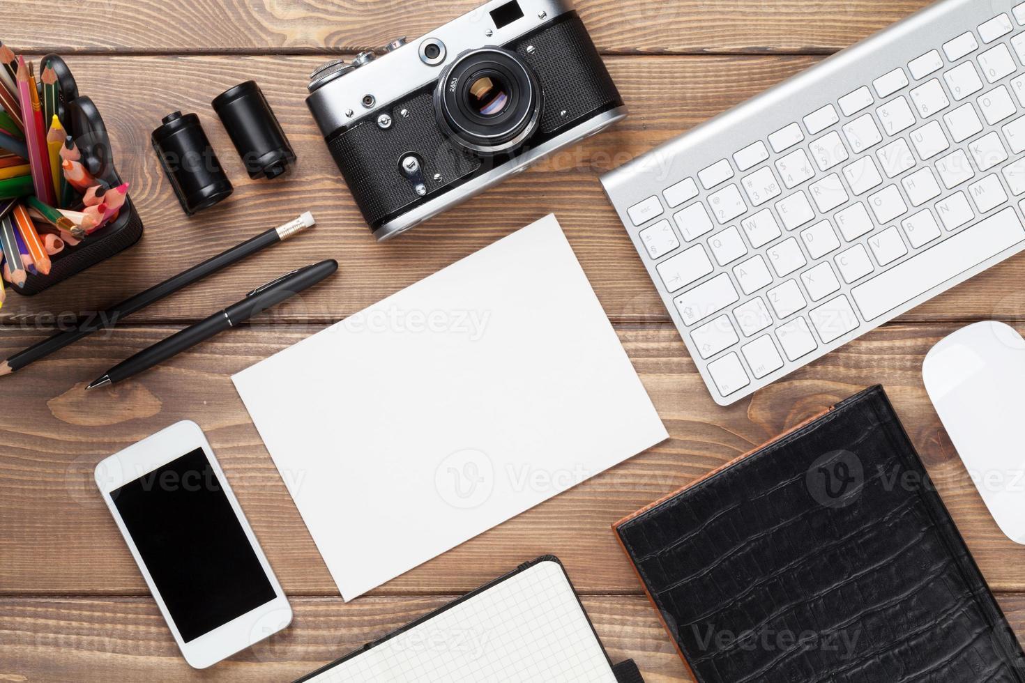 mesa de escritório com suprimentos, câmera e cartão em branco foto
