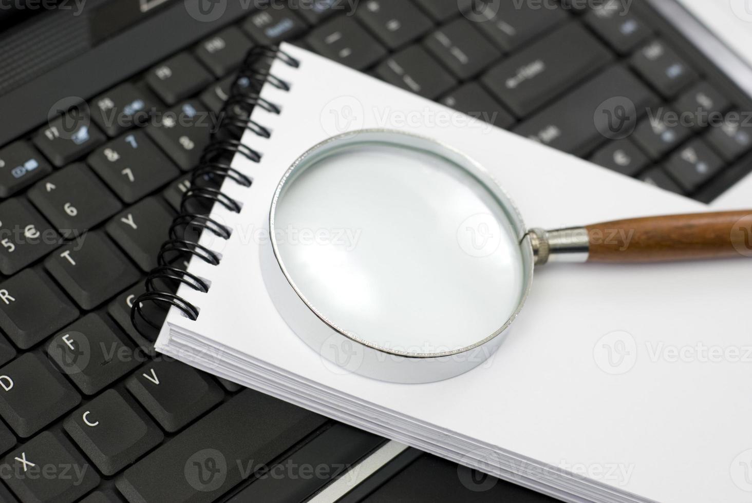 laptop, notebook e lupe em uma mesa foto