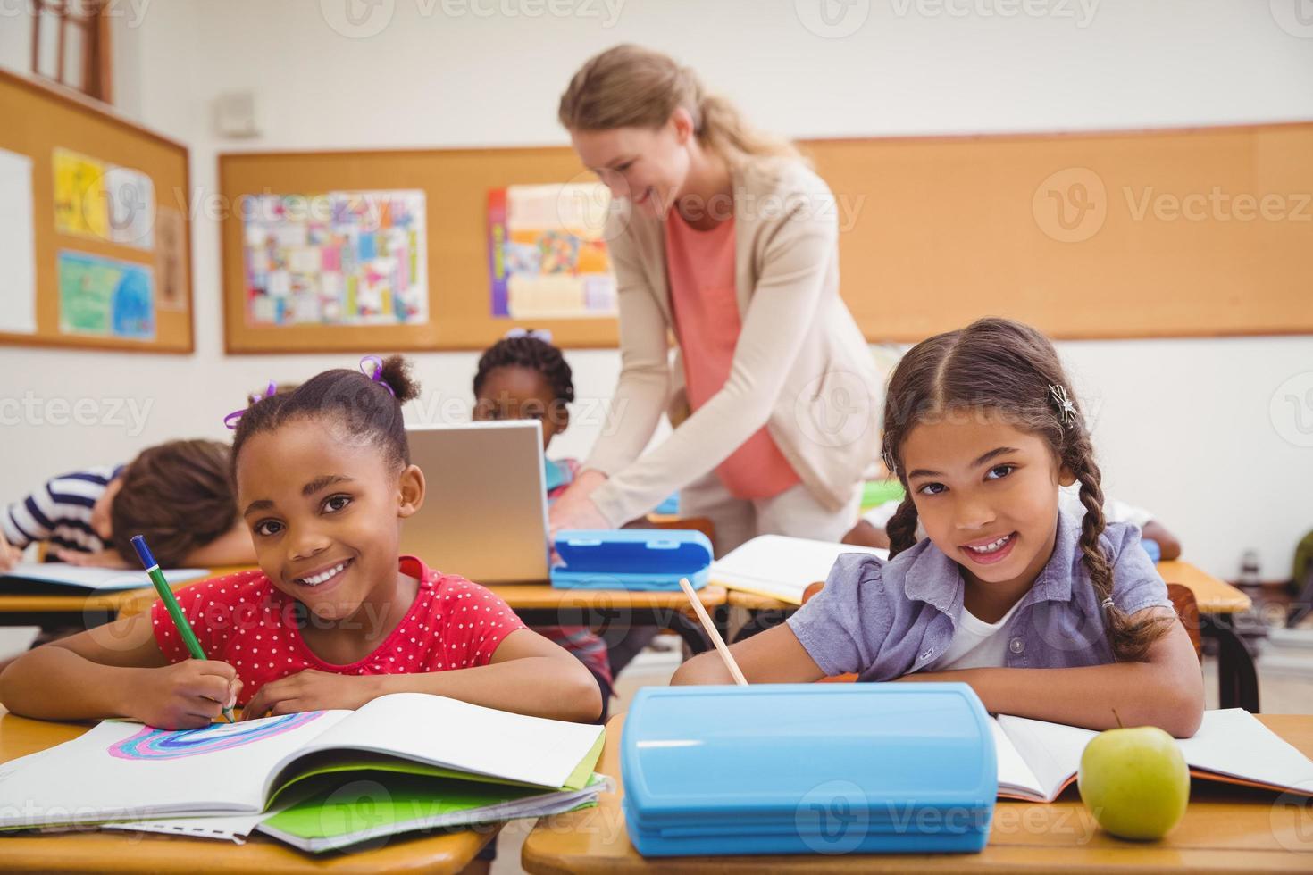 alunos bonitos desenho na mesa na sala de aula foto