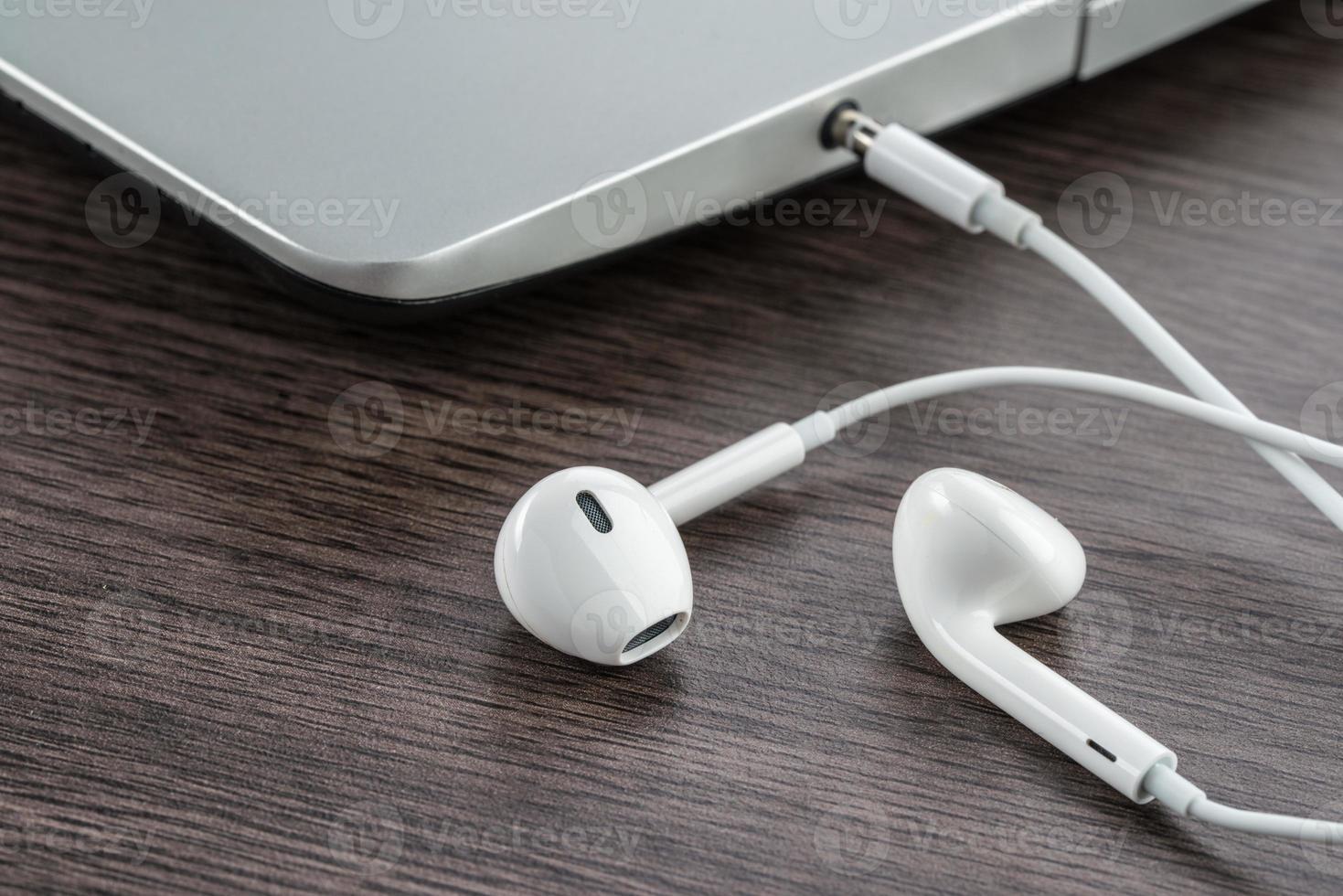 fone de ouvido com o laptop na mesa de madeira foto