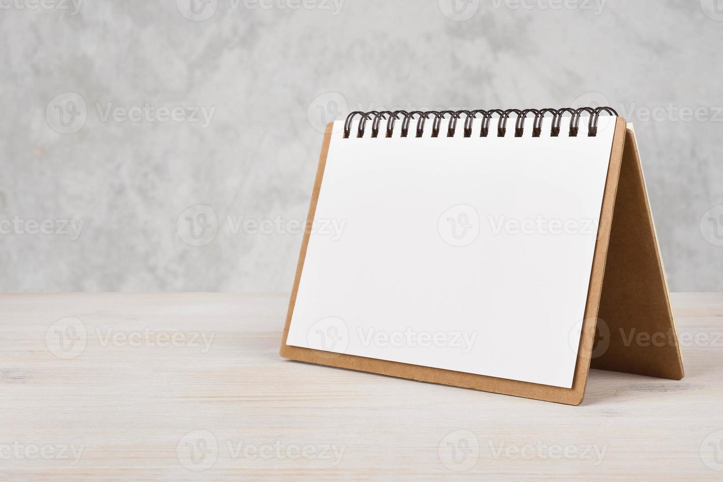 calendário de papel em branco na mesa de madeira foto