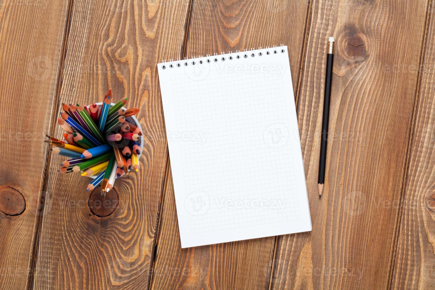 mesa de mesa de escritório com o bloco de notas e lápis coloridos foto