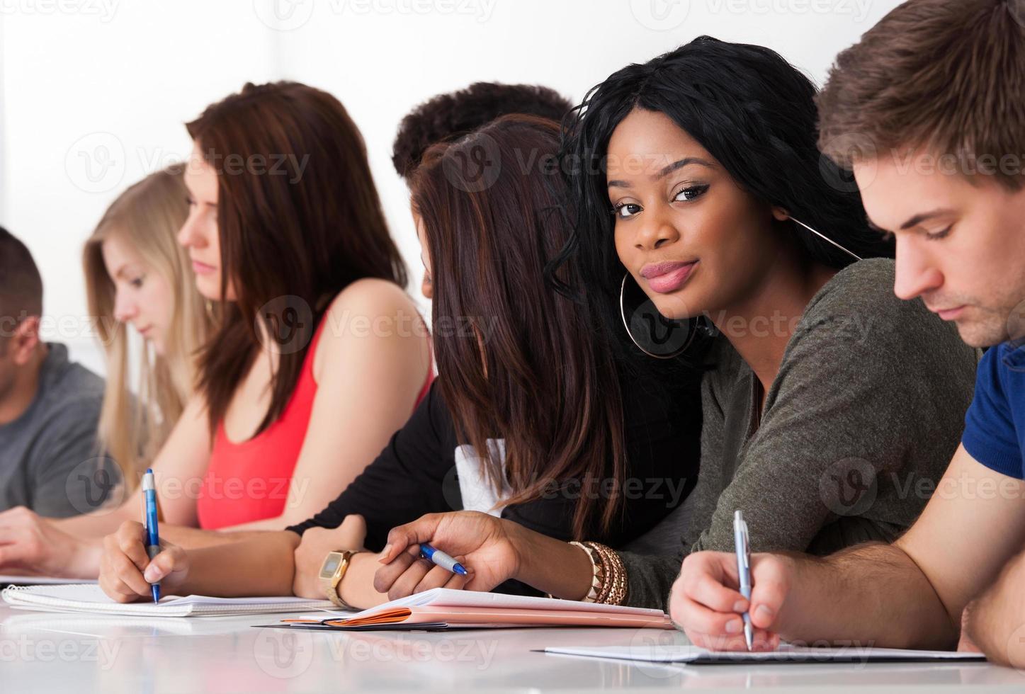 estudante confiante sentado com colegas escrevendo na mesa foto