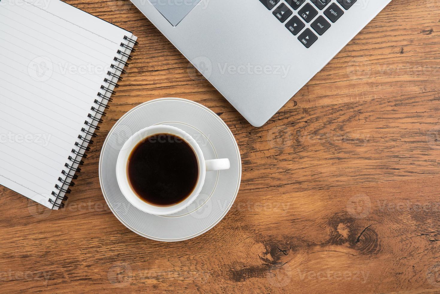 xícara de laptop, notebook e café na mesa de trabalho foto
