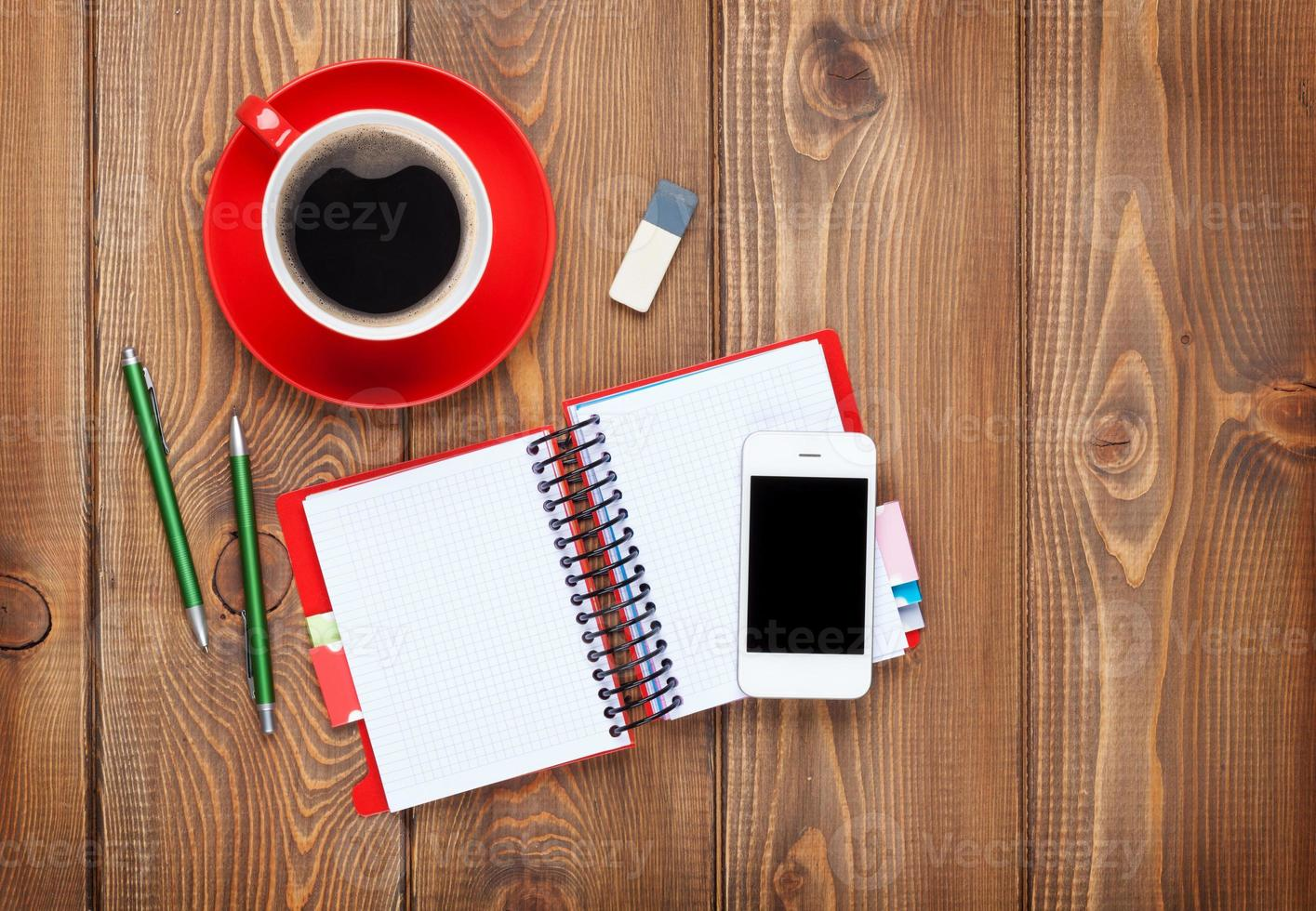 mesa de escritório com suprimentos e xícara de café foto