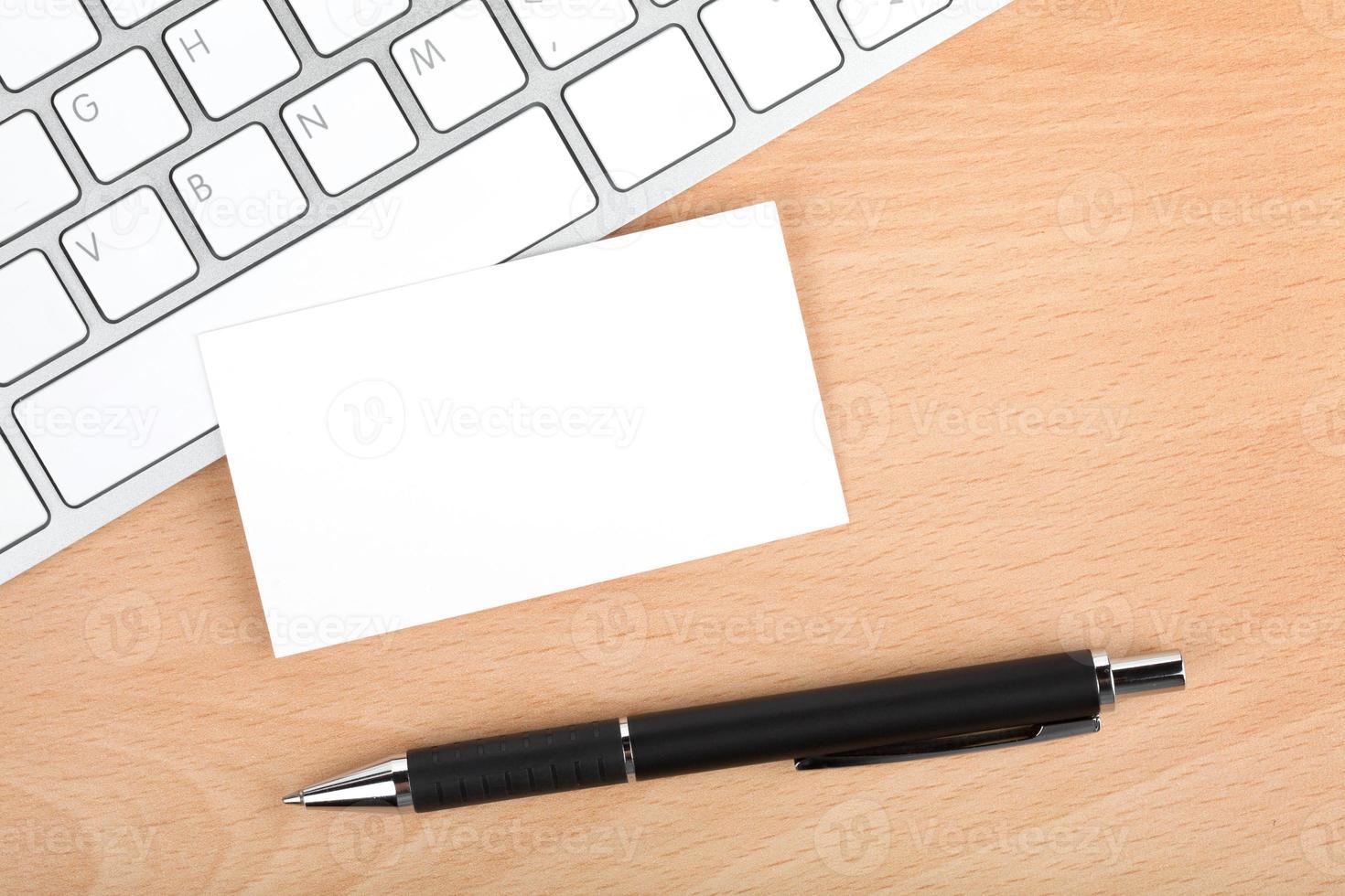 cartões de visita em branco sobre o teclado na mesa de escritório foto