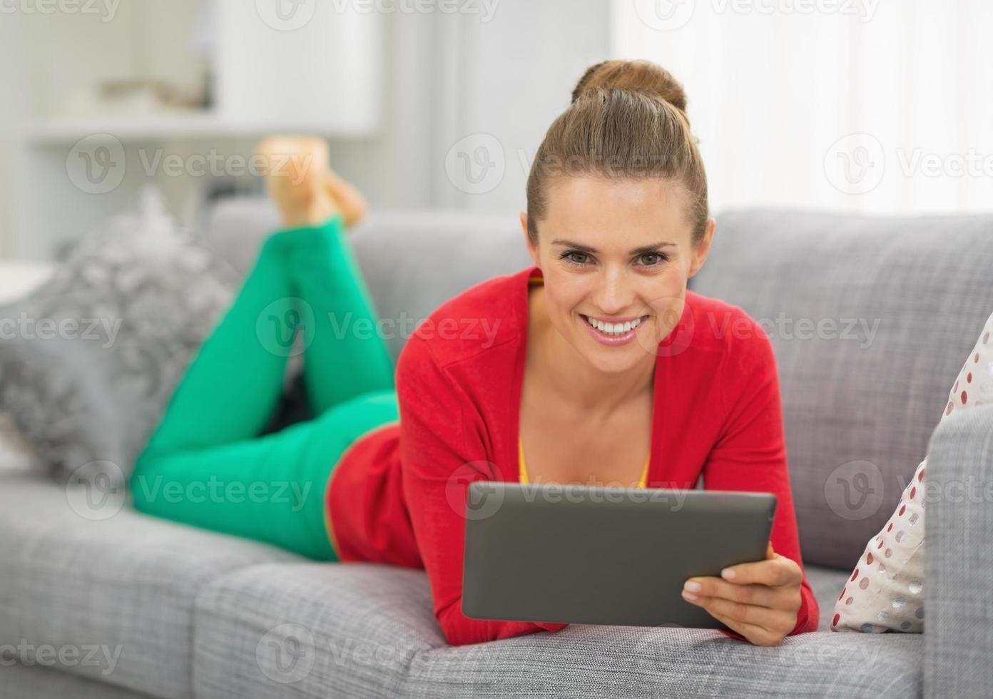 mulher jovem sorridente, deitado no sofá com o tablet pc foto