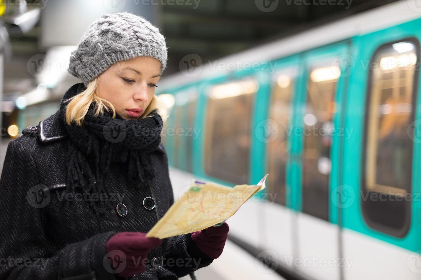 senhora esperando na plataforma da estação de metrô. foto