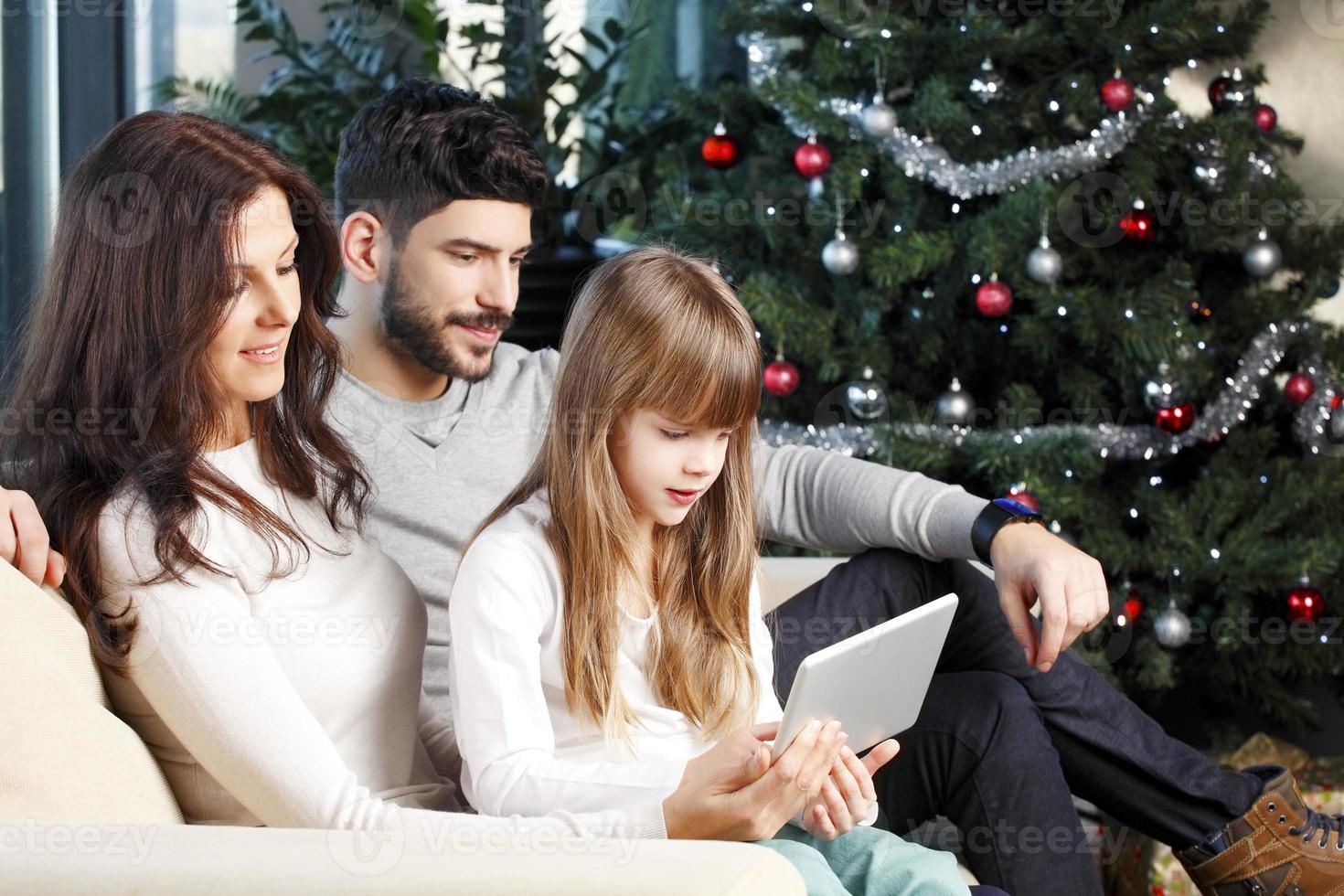 família feliz na árvore de natal foto