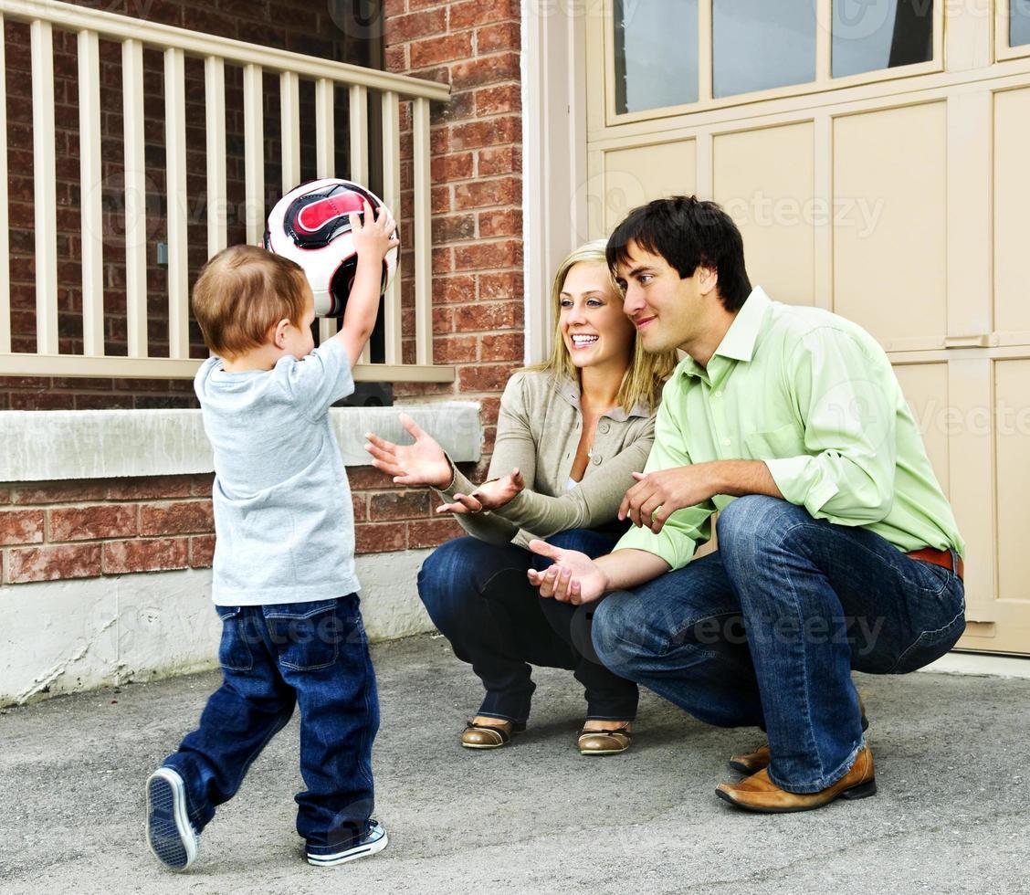 família brincando com bola de futebol foto