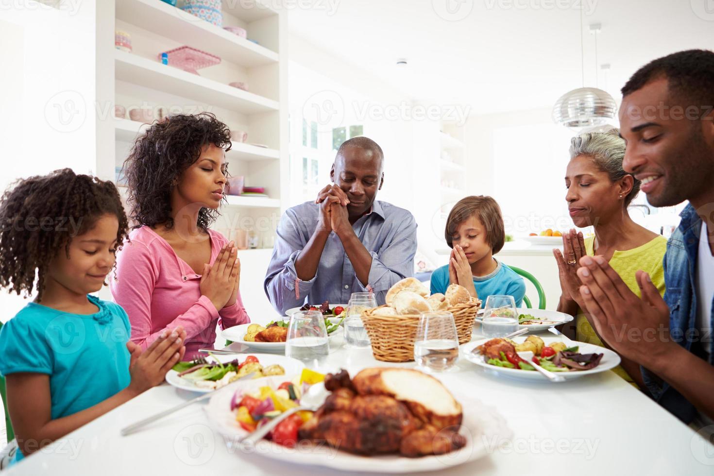 família afro-americana de geração multi rezando em casa foto
