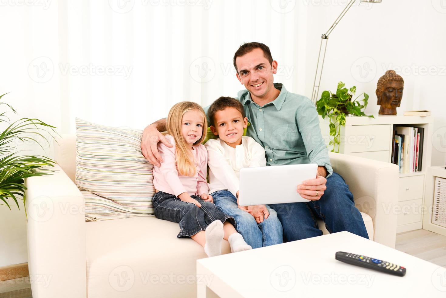 pai feliz brincando com tablet digital com crianças em casa foto