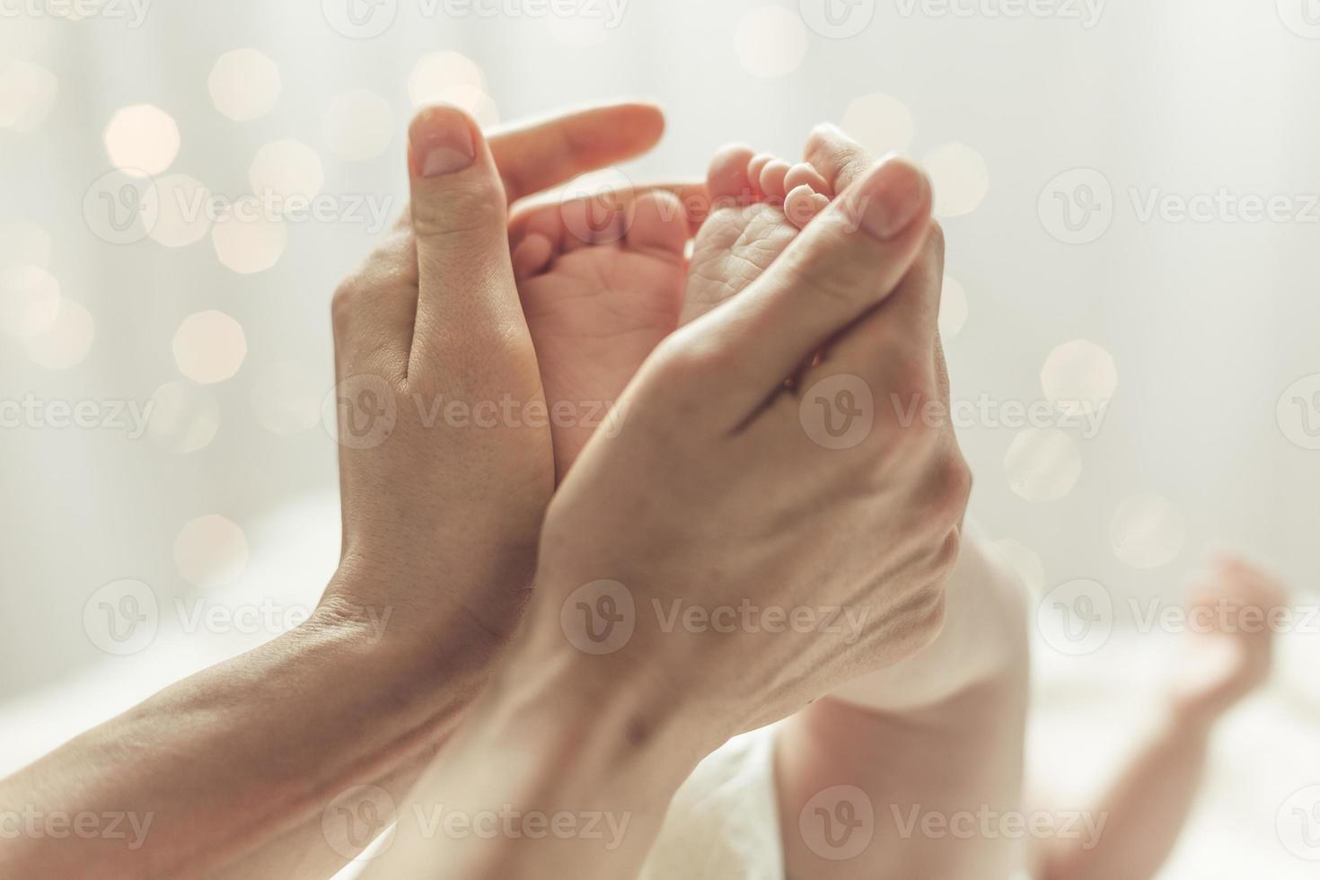 mãe tocando os pés do recém-nascido foto