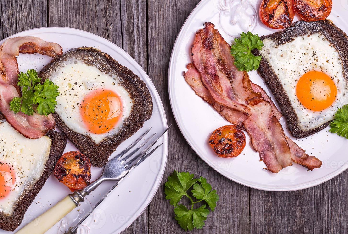 ovos fritos em pão de centeio com bacon, em estilo rústico. foto