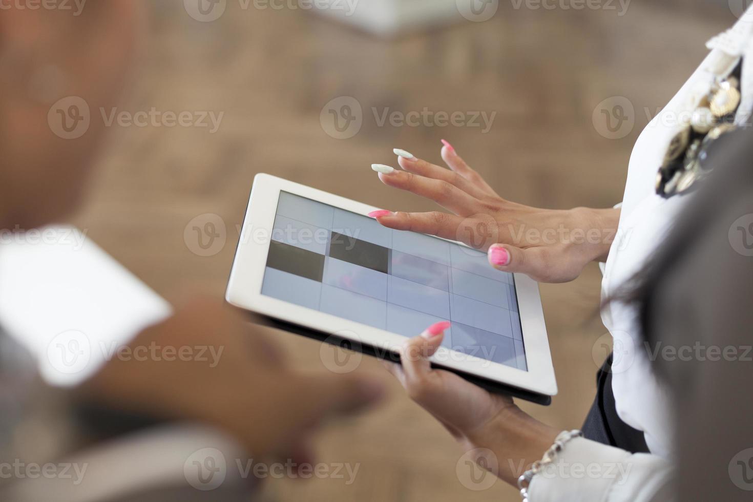 mãos de uma mulher casual, segurando um tablet digital. foto