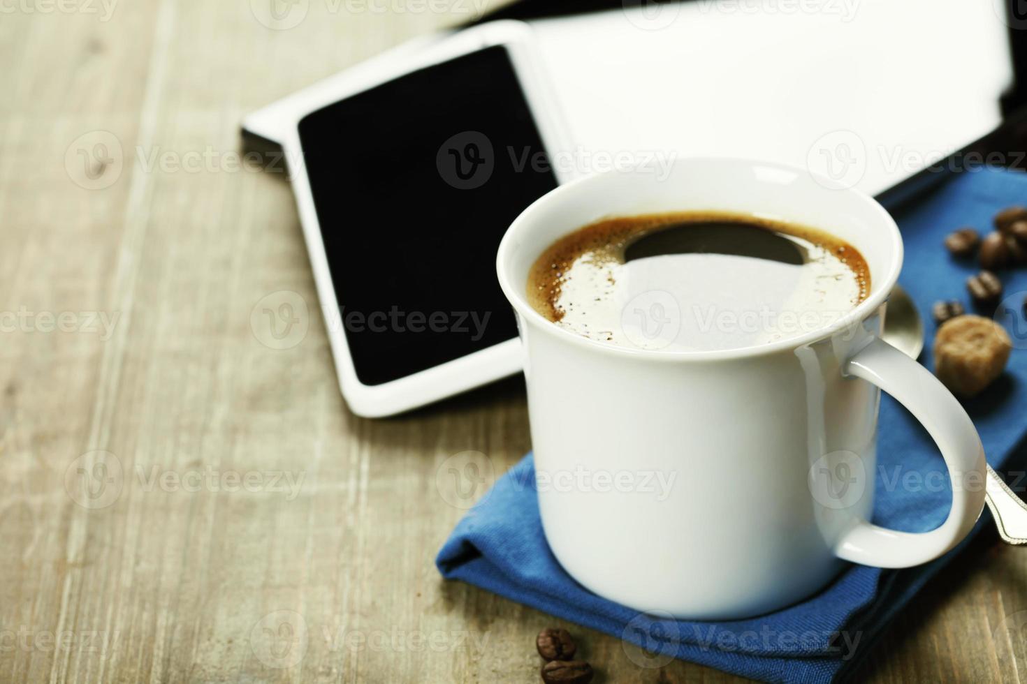xícara de café com computador tablet digital e telefone inteligente foto