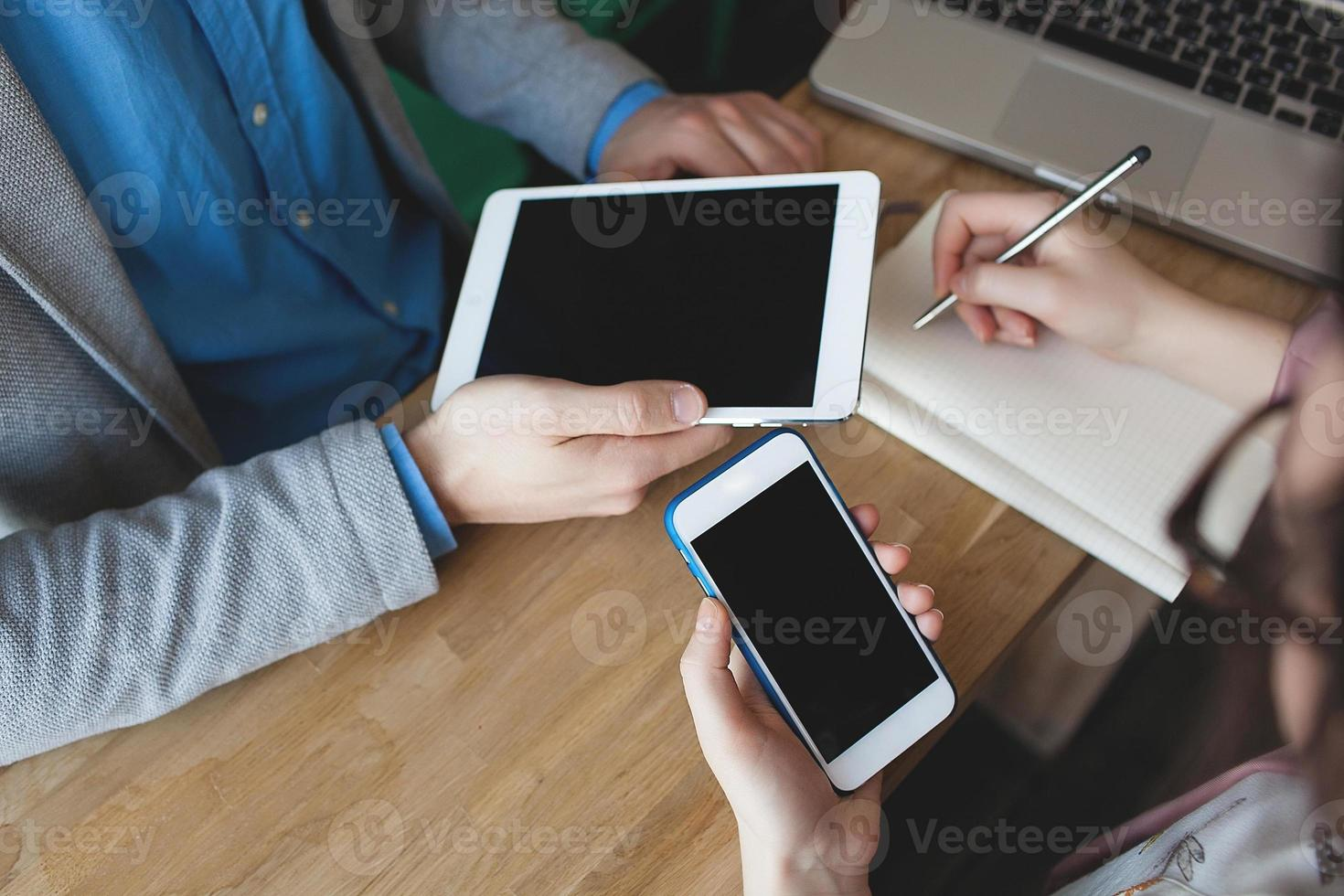 smartphone, tablet e laptop com o bloco de notas nas mãos foto