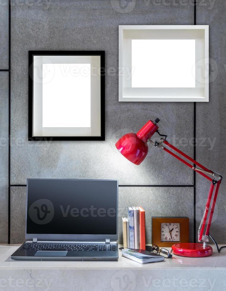 mesa de escritório moderna com laptop, lâmpada e molduras em branco foto