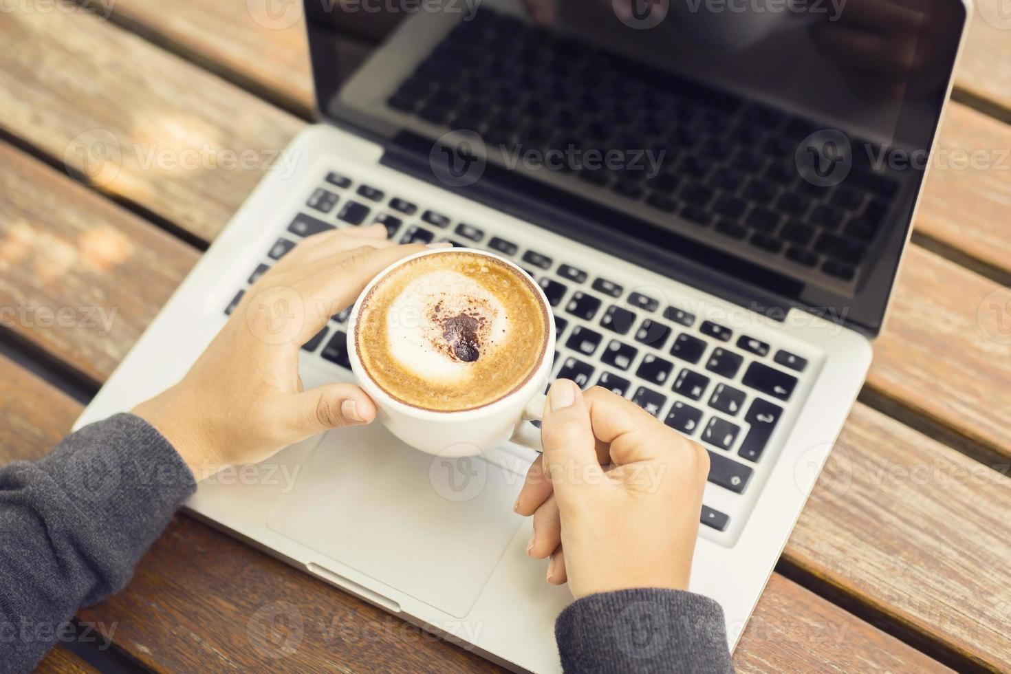 laptop e cappuccino em uma mesa de madeira foto