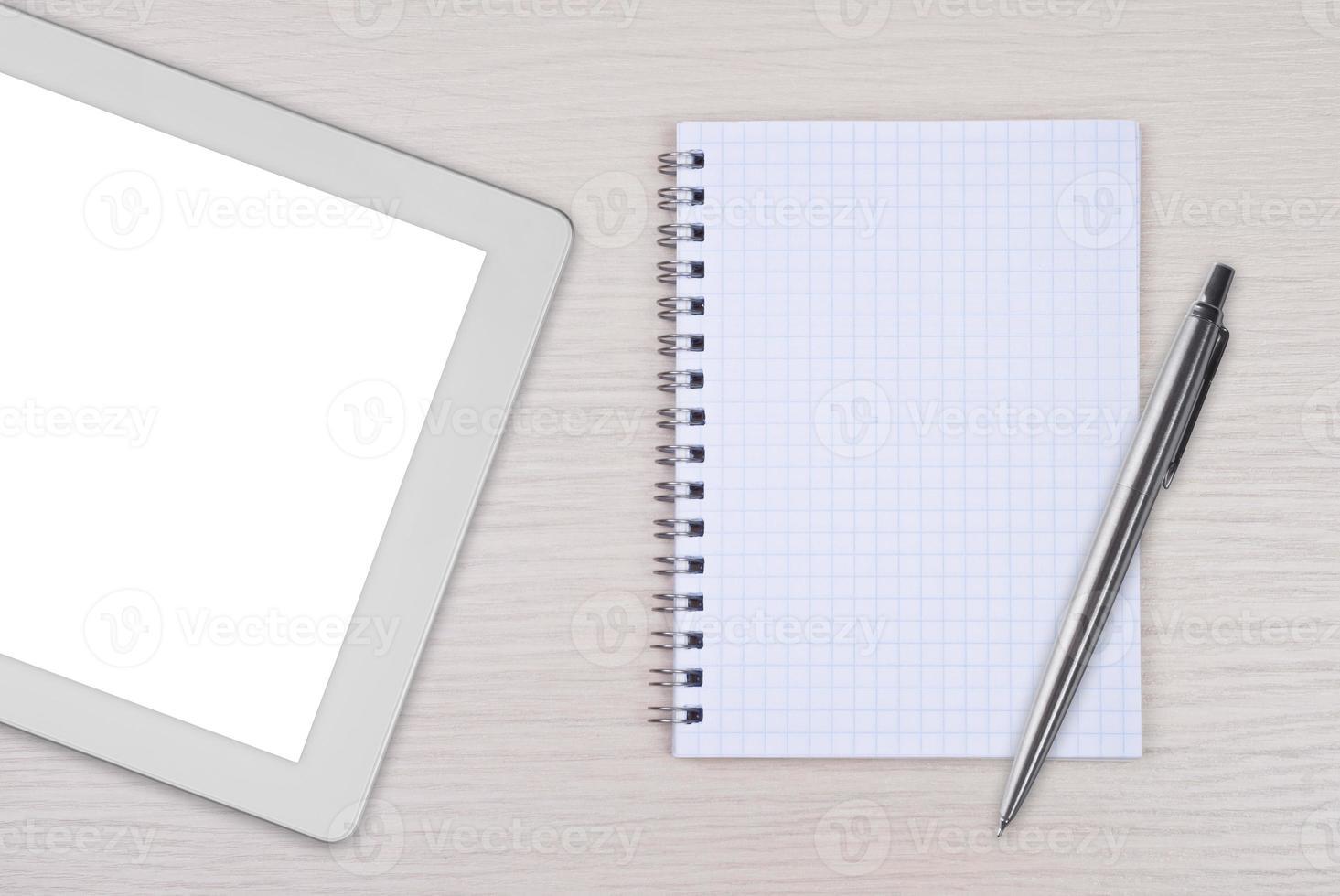 tablet pc com bloco de notas e caneta na mesa de madeira foto