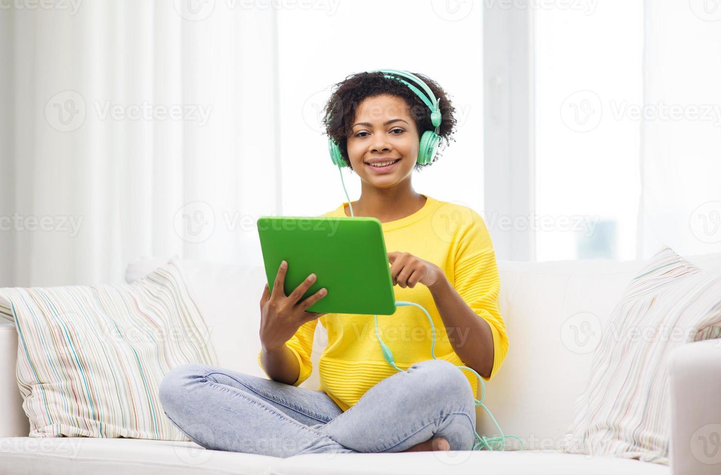feliz mulher africana com tablet pc e fones de ouvido foto