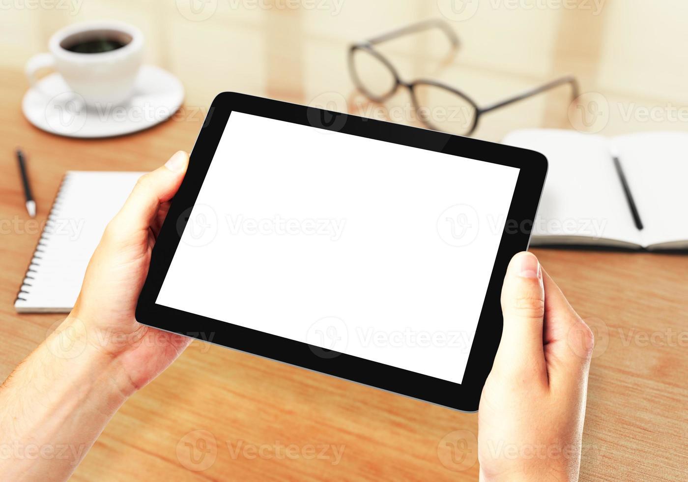 mãos segurando um tablet, óculos e cadernos no fundo foto