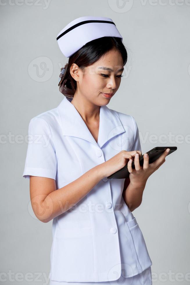 jovem enfermeira asiática tocar uma tela do tablet pc foto